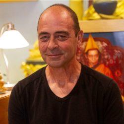 Hombre sonriendo con fondo de altar budista