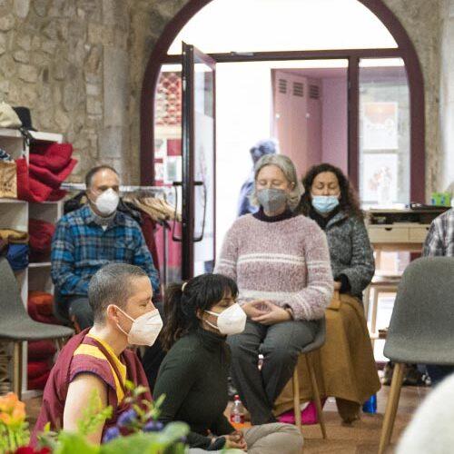 personas realizando una practica de meditación con mascarillas