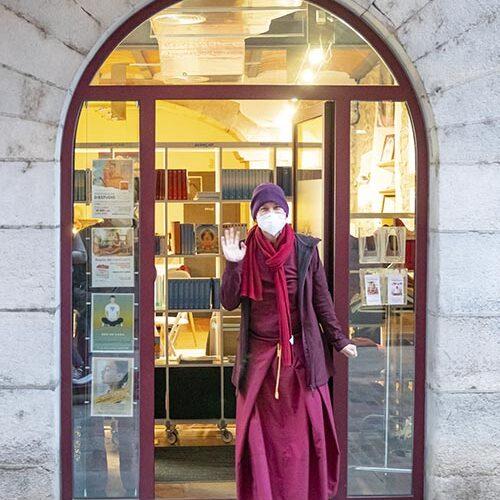 monja budista saludando paradad en la puerta del centro de meditación