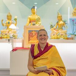 monja budista sentada y un altar con budas de fondo